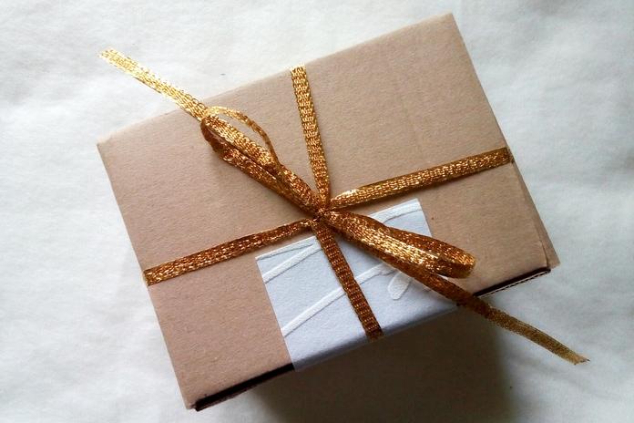 Darilo v kartonasti škatlici; trakec in modra tapeta sta ponovno uporabljena.